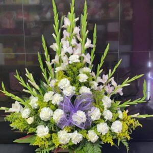 Ramo funebre en gladiolos, claveles blancos, solidago y moño en tela